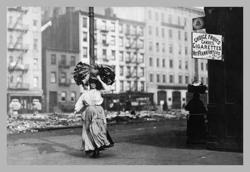 Immigrant Woman Walks Down Street Carrying a Pile of Clothing on Her Head (Canvas Art)